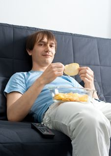 Free Young Man Watching Tv And Eating Chips Royalty Free Stock Photos - 19539838