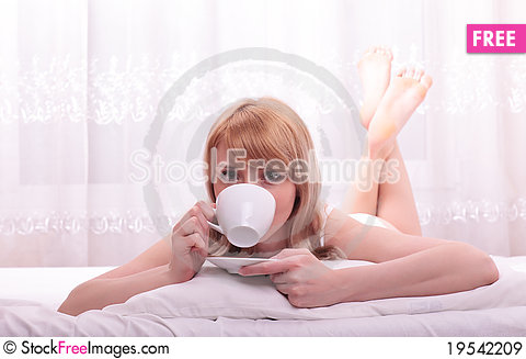 Free Cute Woman Drinking A Coffee Lying Royalty Free Stock Images - 19542209