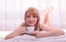Cute Woman Drinking A Coffee Lying Royalty Free Stock Photo