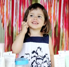 Little Girl Putting Moisturizer On Her Face Royalty Free Stock Photos