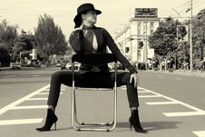Free Woman In A Suit Sitting On A Chair On A Highway Royalty Free Stock Image - 19561276