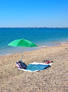 Free Umbrella And Clothes On A Beach Royalty Free Stock Photography - 19567607
