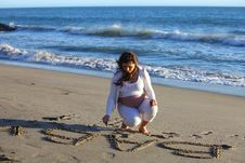 Free Pregnant Woman At Beach Writing  Baby In The Sand Stock Photos - 19580203