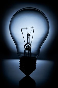 Light Bulb On Black Background With Blue Light Stock Photo