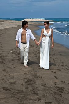 Free A Young Couple Walk On A Beach Royalty Free Stock Photography - 19585017
