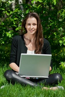 Free Young Woman Sitting In Park And Using Laptop Royalty Free Stock Photography - 19601637