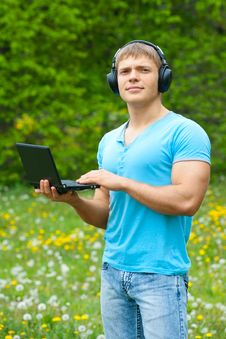 Free Young Man Using A Laptop And Listening Music Stock Photography - 19601682