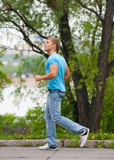 Free Young Man Running Through Park Stock Photos - 19615493