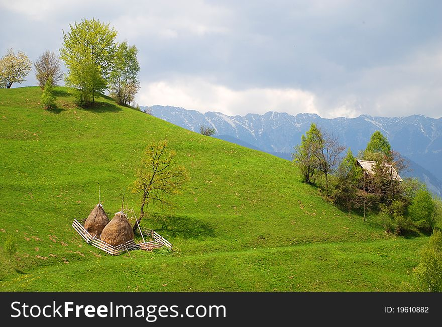 House and haystacks on beautiful hills