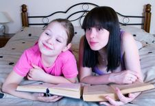 Mother And Daughter Reading In Bed Book Stock Image