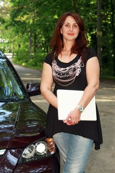 The Woman With  Laptop Costs Near The Car Royalty Free Stock Photo