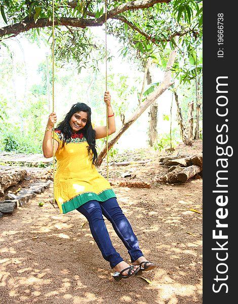 Beautiful Young Girl in Yellow Dress Fun on Swing