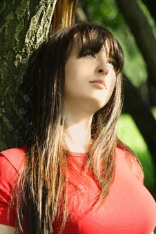 Girl Sitting Near Tree Stock Images