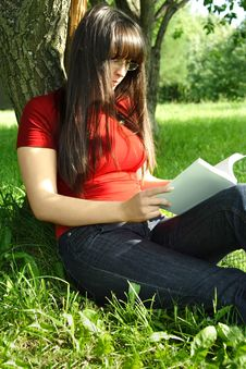 Girl Sitting Near Tree And Reading Book Royalty Free Stock Photos