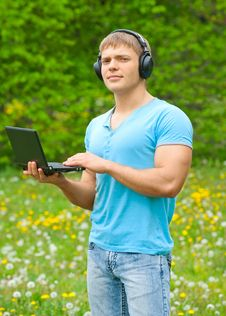 Free Young Man Using A Laptop And Listening Music Royalty Free Stock Image - 19718016