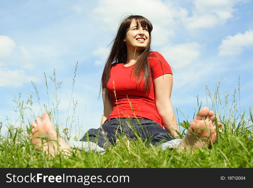 Barefooted women siting on summer meadow