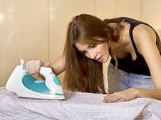 Young Woman Ironing On Ironing Board Stock Images