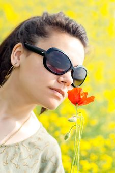 Free Brunette Girl Smelling A Corn Poppy From Her Hand Stock Image - 19761961