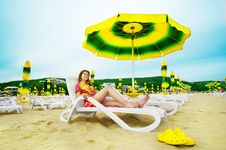 Beautiful Woman Laying On The Beach Under Umbrella Royalty Free Stock Images