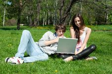 Free Couple Sitting In Park And Using Laptop Royalty Free Stock Image - 19794486