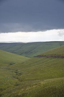 Green Hills Below Storm Clouds Royalty Free Stock Photography