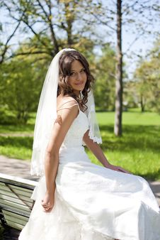 Beautiful Young Bride Sitting On Bench Royalty Free Stock Images