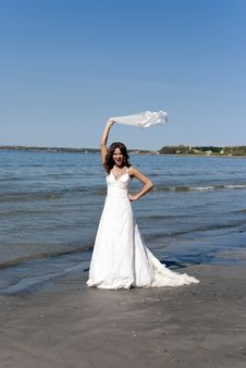 Free Bride Twirling The Veil Near The Sea Royalty Free Stock Images - 19852389