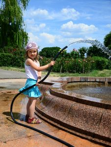 Little Girl With A Hose Stock Photo