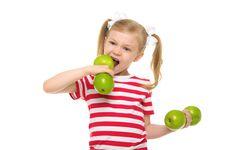 Girl Bites Dumbbell From Apples Royalty Free Stock Image