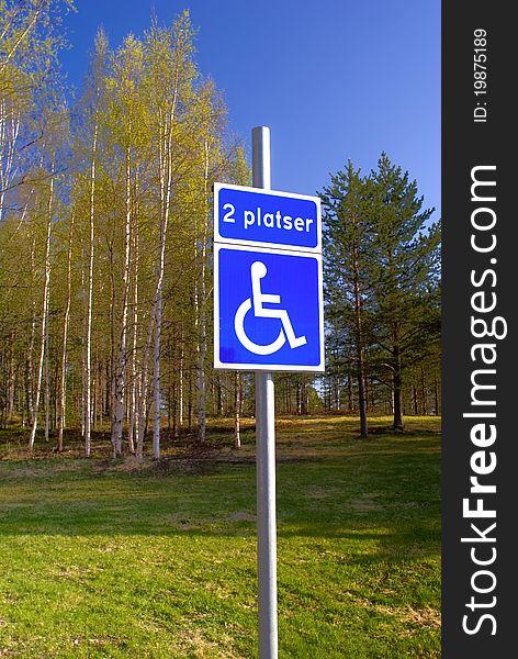 Disabled parking sign on green park