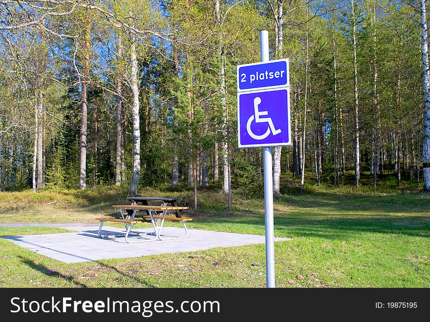 Bench in the park and a sign for disabled