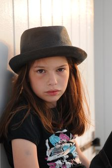 Young Girl Wearing Black Hat Against Beach Cabin Royalty Free Stock Photography