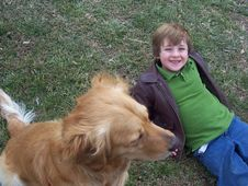 Boy And Golden Retriever In Field Royalty Free Stock Images
