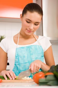 Free Young Woman Cutting Vegetables In A Kitchen Royalty Free Stock Photography - 19902717