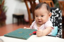 Free 7 Month Old Asian Baby Girl, Holding The Menu Stock Images - 19927954