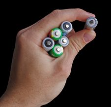 Hand Holding An AA Batteries Isolated On Black