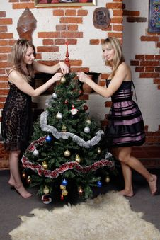 Free Two Young Beautiful Girls Decorate Christmas Tree Stock Photography - 20007452