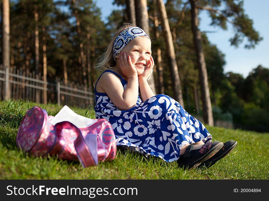 Merry beautiful girl sitting on green grass