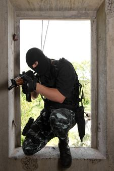 Soldier In Mask Entering The Window With Ak-47 Stock Images