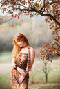 Free The Red-haired Girl In Autumn Leaves Stock Images - 20039424