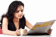 Free Smiling Indian Teen Reading Newspaper With Coffee Royalty Free Stock Photography - 20030637