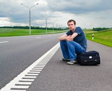The Young Man Sits Pending On Road Stock Images