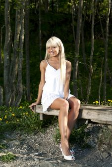 Free Girl Sitting On A Bench In The Woods Stock Photos - 20051773