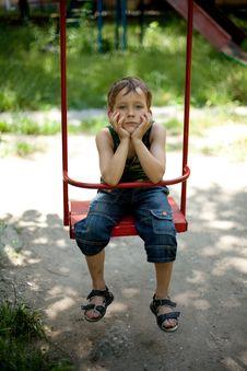 Little Boy Sitting On A Swing Stock Image