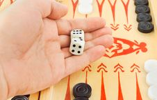 Hand With Dices And Backgammon Royalty Free Stock Image
