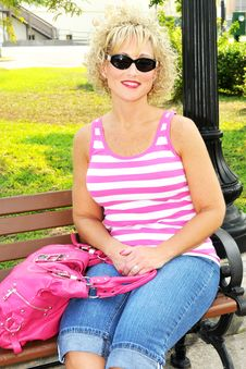 Free Adult Woman Siting On A Park Bench With Pink Purse Royalty Free Stock Images - 20056479