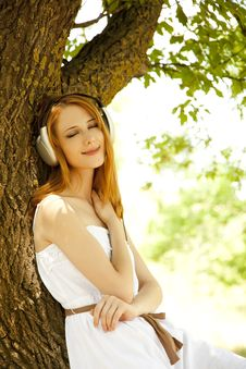 Redhead Girl With Headphones At Garden. Royalty Free Stock Photo