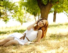 Redhead Girl With Headphones At Garden. Stock Images