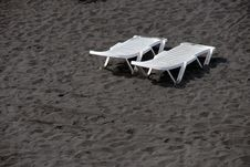 Free Lounge Plastic White Beds On Black Sand Beach Stock Photography - 20066922