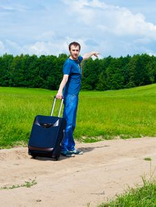 The Young Man On Road In Field With A Suitcase Royalty Free Stock Photo